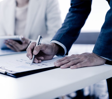 man in suit leaning on table signing document