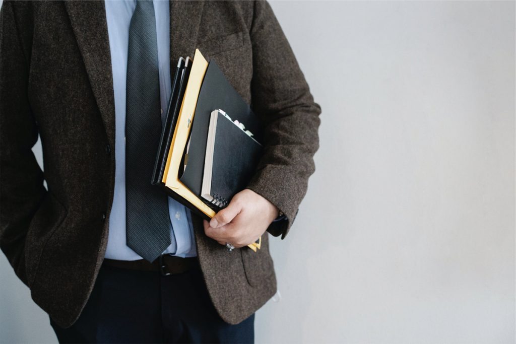 man in suit holding notepad with hand in pocket