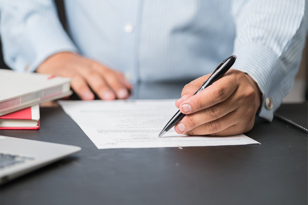 man in shirt holding pen to paper